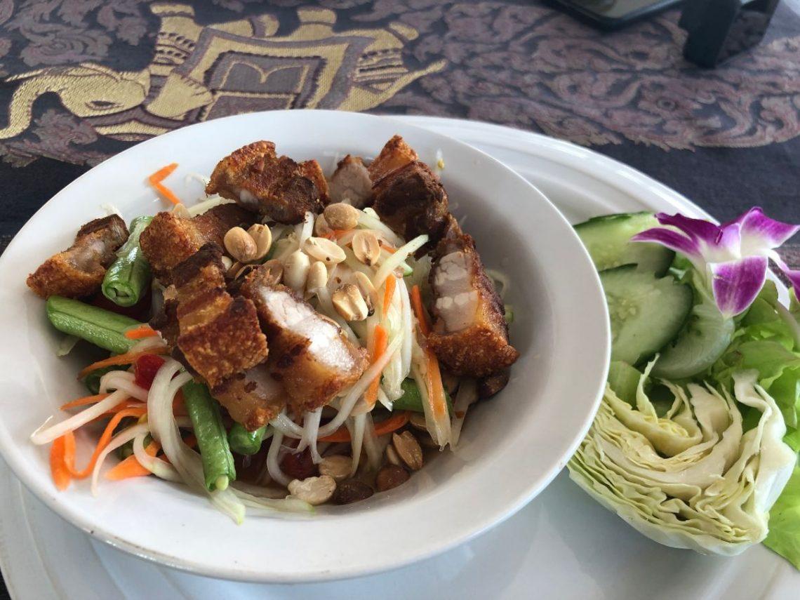 plate with papaya salad and crispy pork